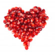 Pomegranate seeds as heart shaped isolated on white — Stock Photo