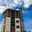 Crane and the house under construction against the blue sky with white clouds in the summer sunny day - Stock Photo