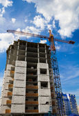 Crane and the house under construction against the blue sky with white clouds in the summer sunny day — Stock Photo