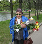 A woman veteran with flowers at the Piskaryovskoye cemetery on May 9 — Stock Photo
