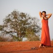 Beautiful girl dressed  terracotta dress - Stock Photo