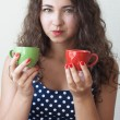 Young beautiful brunette holding two cups - Stock Photo