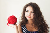 A beautiful young brunette with a ball of thread in their hands — Stock Photo