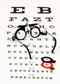 Glasses lying on optotype test — Stock Photo