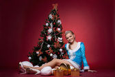 Young sexy snow maiden girl with decorated new year fir tree on red - look at camera — Stock Photo