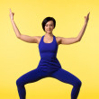 Young woman in blue doing yoga asana on yellow — Stock Photo