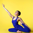 Woman doing yoga split in blue on yellow — Stock Photo