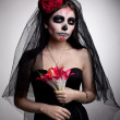 Serious woman in skull face art mask and flowers — Stock Photo #8170232