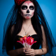 Serious woman in skull face art mask and flowers — Stock Photo #8501780