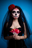 Serious woman in skull face art mask and flowers — Stock Photo