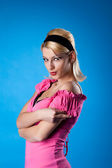 Pretty woman pin-up portrait in rose on blue — Stock Photo