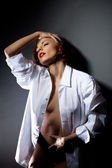 Desired young woman in sexy shirt on black wall — Stock Photo