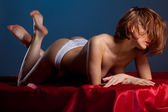 Desired young woman in sexy panties on red silk — Stock Photo