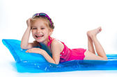 Cute little girl in a swimming suit on an inflatable mattress — Stock Photo