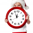 Cute little girl in santa cap with a clock — Stock Photo