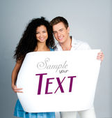 Couple holding a paper with sample text — Stock Photo