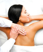 Pretty woman relaxing while getting a back massage — Stock Photo