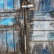 Old rotten door with blue paint - Stock Photo