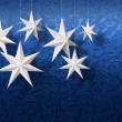 White paper stars on blue brocade — Stock Photo #9324985