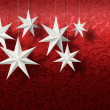 White paper stars on red brocade — Stock Photo