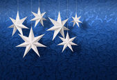 White paper stars on blue brocade — Stock Photo