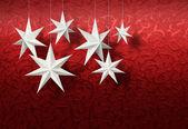 White paper stars on red brocade — Stock Photo