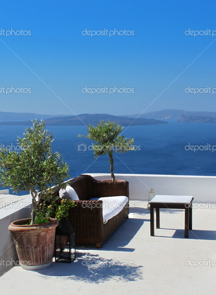 Vacation terrace with sofa and table above blue sea — Stock Photo #9324655