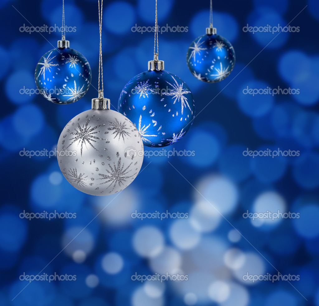 Blue and silver Christmas balls hanging against blue light spots background  Stock Photo #9352260