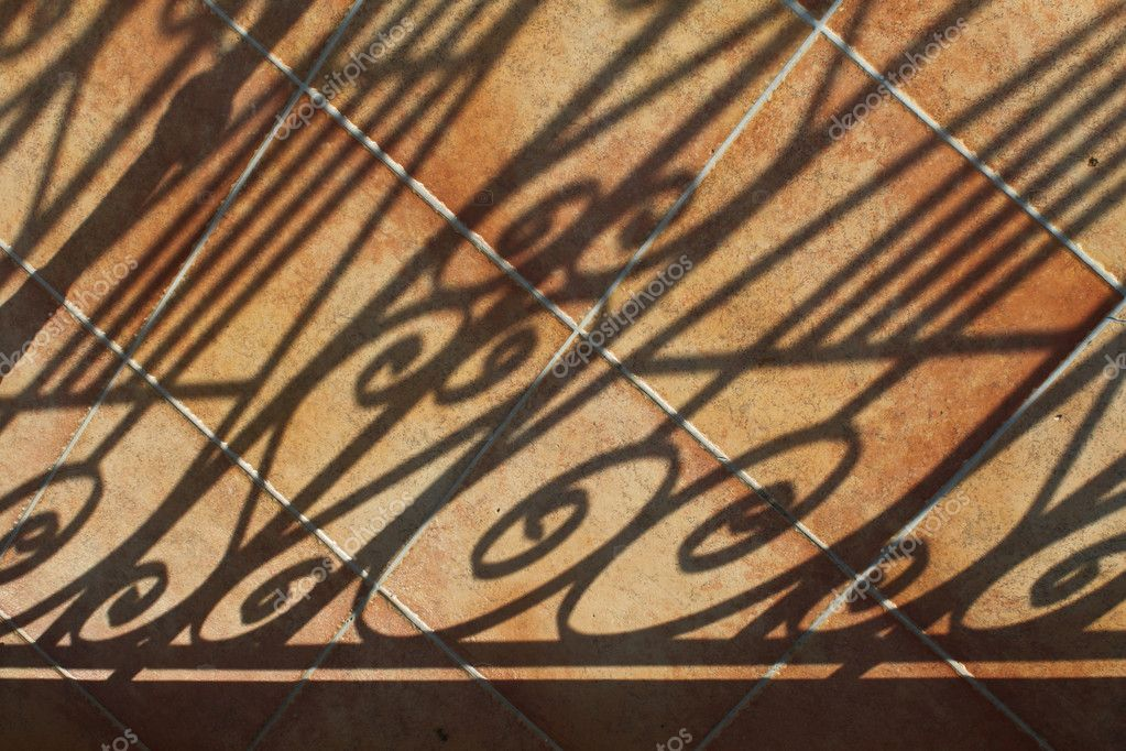 Decorative curly shadows falling on tiled terracotta patio — Stock Photo #9352648