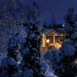 Illuminated house on snowy Christmas evening — Stock Photo
