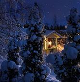 Illuminated house on snowy Christmas evening — Stock Photo
