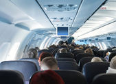 Passengers in airplane cabin interior — 图库照片