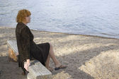 Pensive lady looking at the lake — Stock Photo