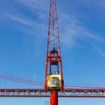 Red crane and red metallic bridge on background — Stock Photo
