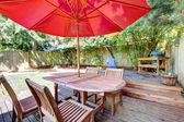 Back yard large deck with red umbrella and chairs. — Stock Photo