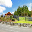 Log cabin house on the hill with road and fence. — Stock Photo