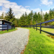 Horse farm with road, fence and shed. — Stock Photo