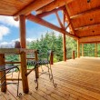 Porch of the log cabin with small table and forest view. - Stock Photo