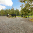 Stock Photo: Horse farm gravel road with three gates.