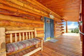 Wood log cabinet porch with entrance and bench. — Stock Photo