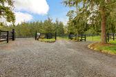 Horse farm gravel road with three gates. — Stock Photo