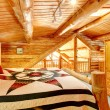 Log cabin bedroom under wood large ceiling. - Stockfoto