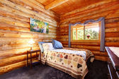 Timmerstuga rustik sovrum med blå gardiner. — Stockfoto