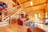 Salle de séjour de cabane en bois rond de luxe avec canapé en cuir. — Photo