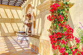 Flowers and fountain on Spanish wall details. — Stock Photo