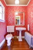 Luxury red and gold small bathroom with silver radiator. — Stock Photo