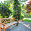 Stock Photo: Front entrance bench with summer landscape.