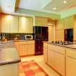 Large kitchen with honey wood and black appliances. — Stock Photo #8741544