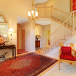 Stock Photo: Luxury entrance living room with red rug, staircase.