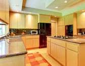 Large kitchen with honey wood and black appliances. — Stock Photo